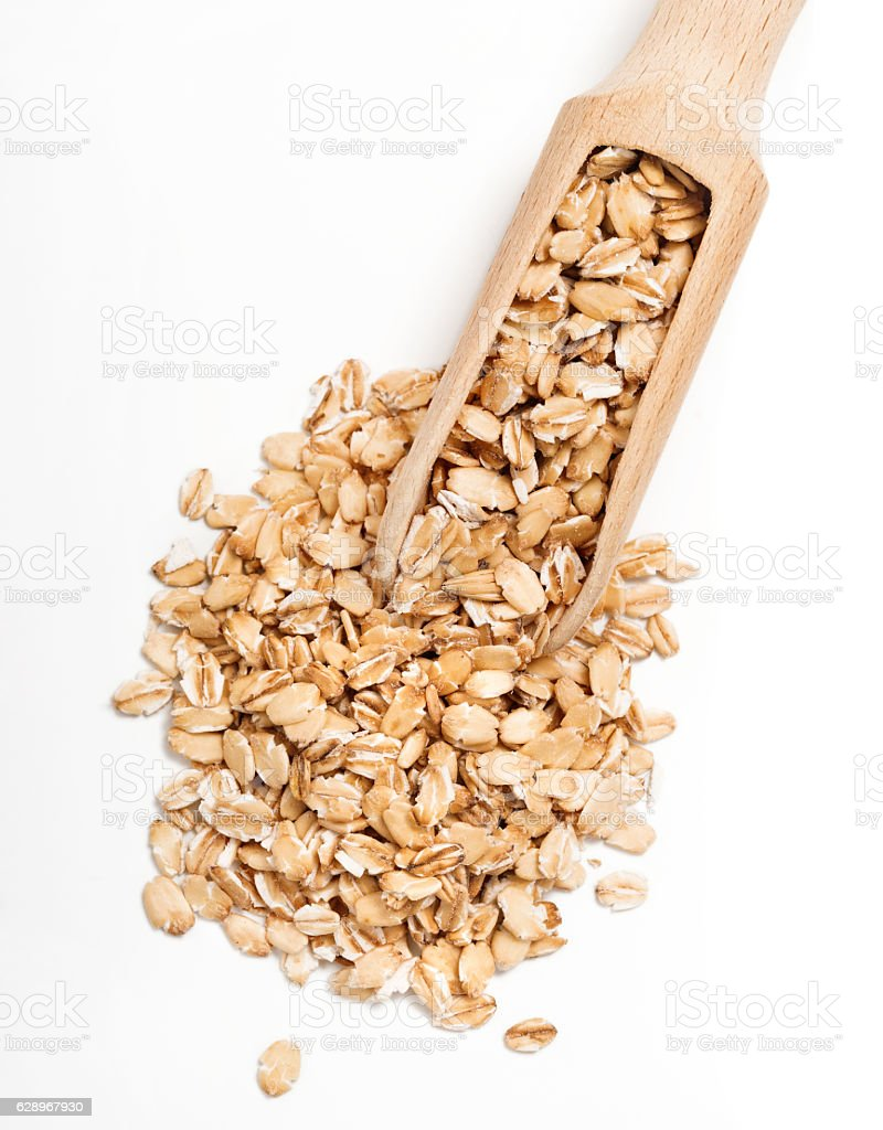 Uncooked oat flakes in wooden scoop stock photo