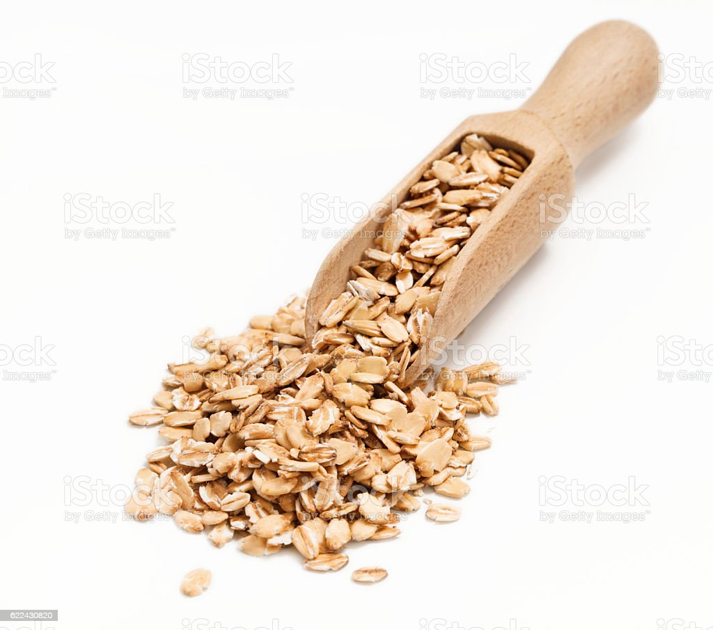 Uncooked oatmeal in wooden scoop stock photo