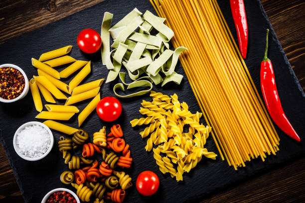 Uncooked pasta and vegetables on wooden background Uncooked pasta and vegetables on wooden background uncooked pasta stock pictures, royalty-free photos & images