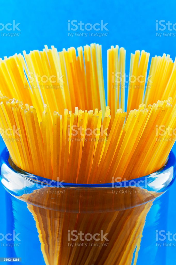 Uncooked pasta spaghetti macaroni on blue background royalty-free stock photo