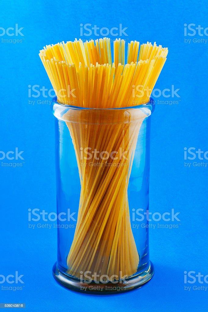 Mano humana espaguetis pasta de macarrones en fondo azul foto de stock libre de derechos