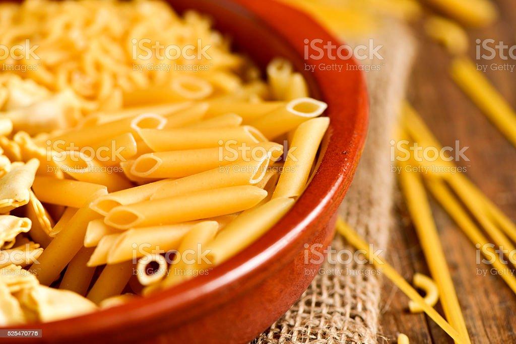 uncooked pasta, such as ravioli, spaghetti or mostaccioli stock photo
