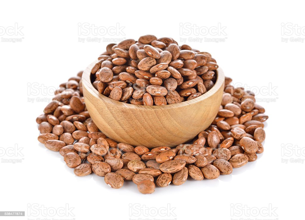uncooked pinto beans in wooden bowl on white background stock photo