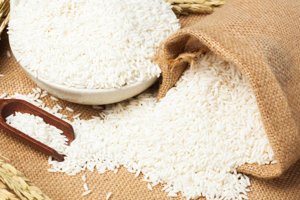 uncooked plain white jasmine rice and wooden spoon. Close up on the table. Horizontal uncooked plain white jasmine rice and wooden spoon. Close up on the table. Horizontal basmati rice stock pictures, royalty-free photos & images
