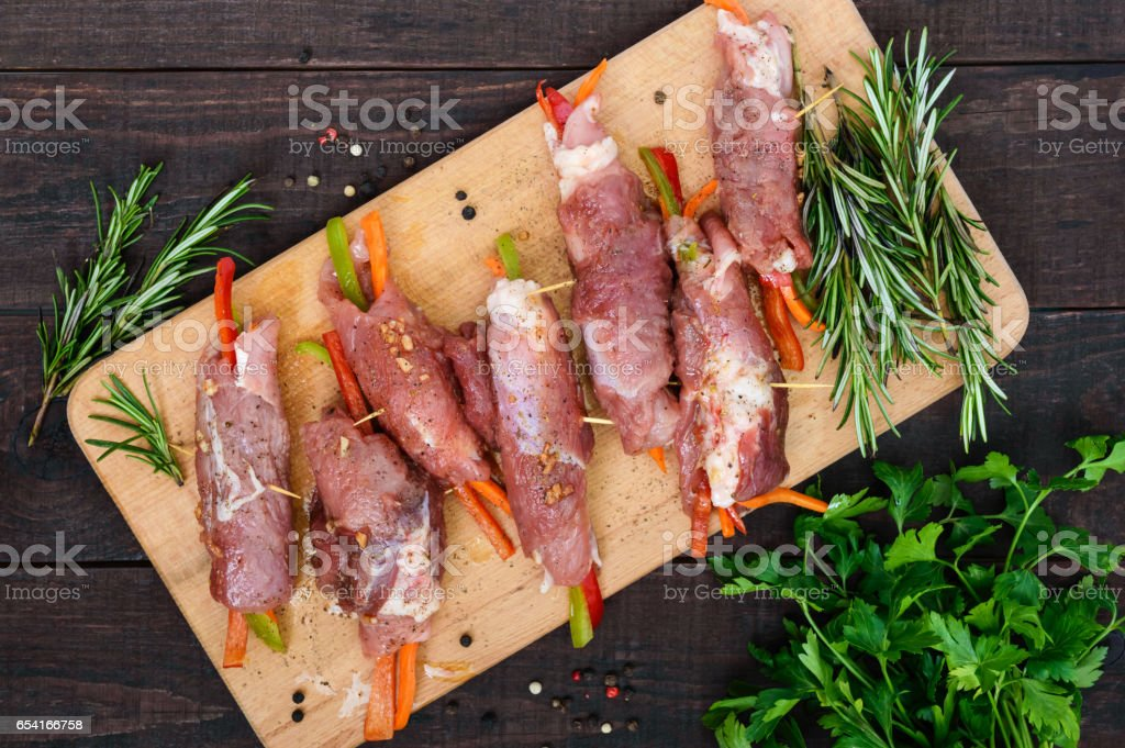 Un-cooked, pork meat rolls stuffed with vegetables (pepper, carrots) in hot garlic sauce on a cutting board. Raw, semi-finished product. The top view stock photo