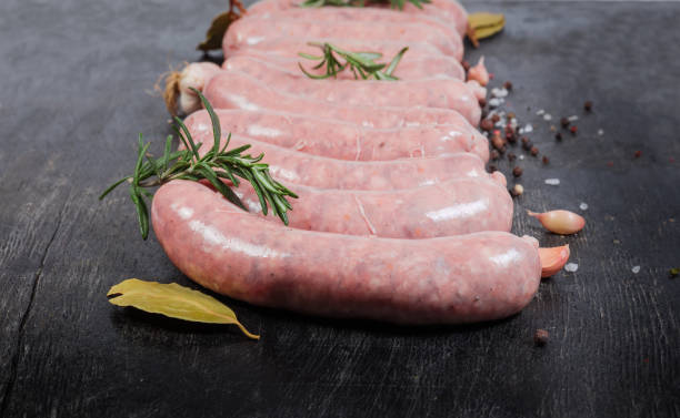 Uncooked pork sausages among spices on dark surface close-up stock photo