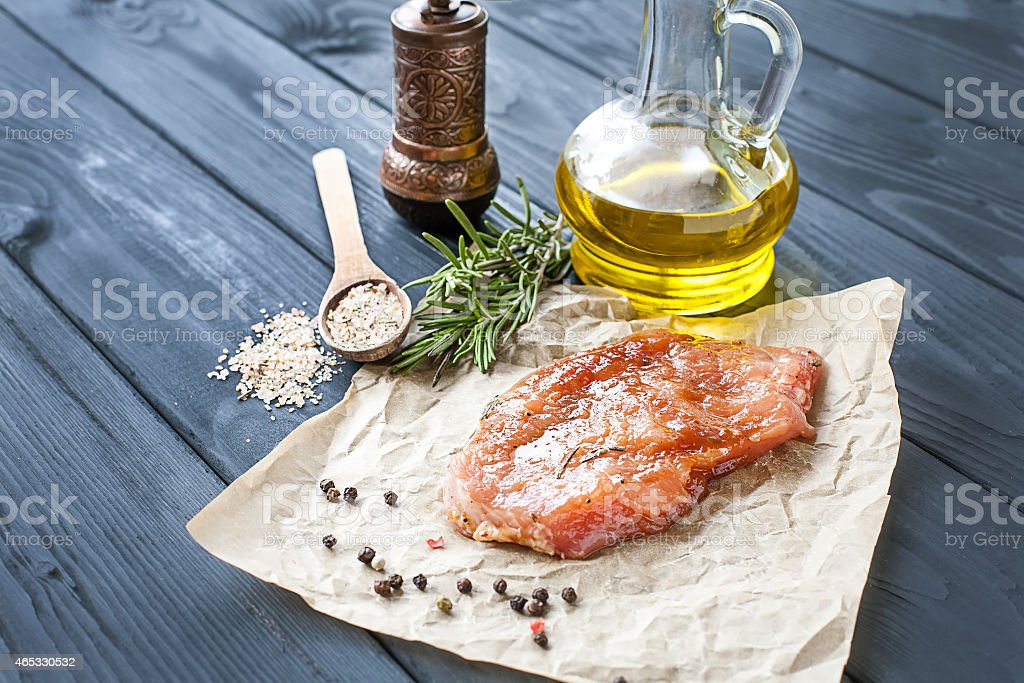 Uncooked pork tenderloin with oil herbs and spices stock photo