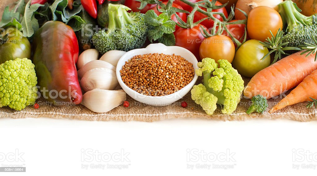 Uncooked red millet in a bowl with vegetables stock photo
