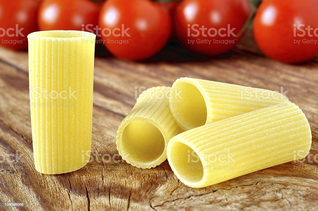 Uncooked rigatoni pasta and cherry tomatoes royalty-free stock photo