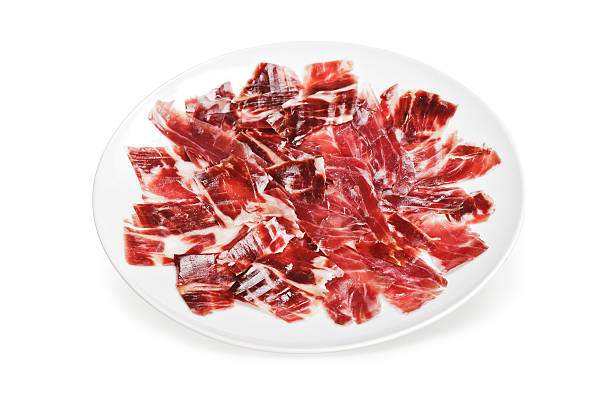 Uncooked slices of Iberico Ham on a round white plate Slices of ham cutted by hand on a white plate over a white background estudio stock pictures, royalty-free photos & images