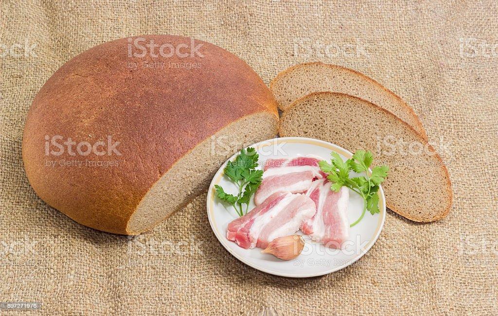Uncooked streaky bacon, sprigs parsley and coriander, garlic, br photo libre de droits