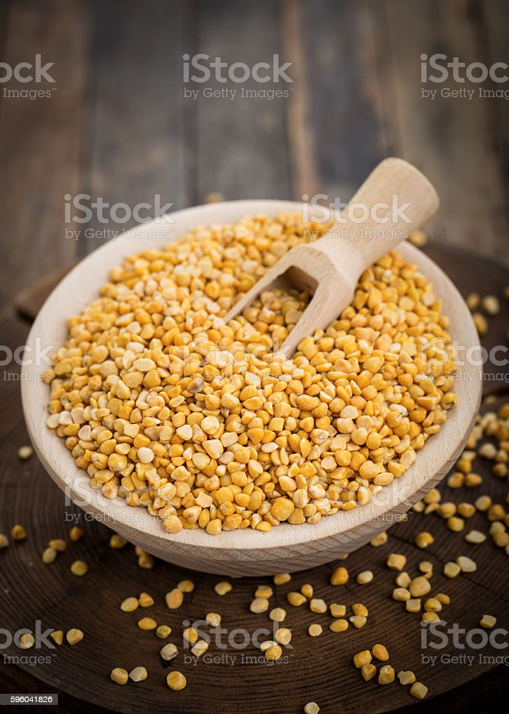Uncooked yellow lentils in the wooden bowl stock photo