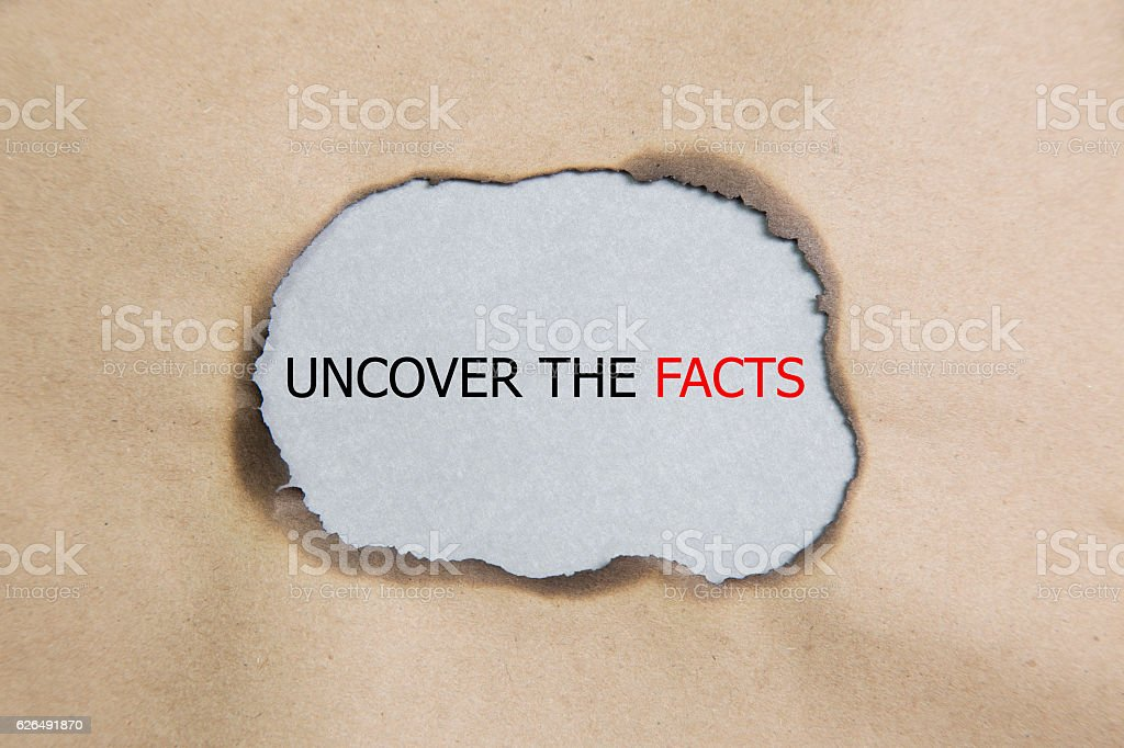 Uncover the facts concept phrase under torn paper stock photo