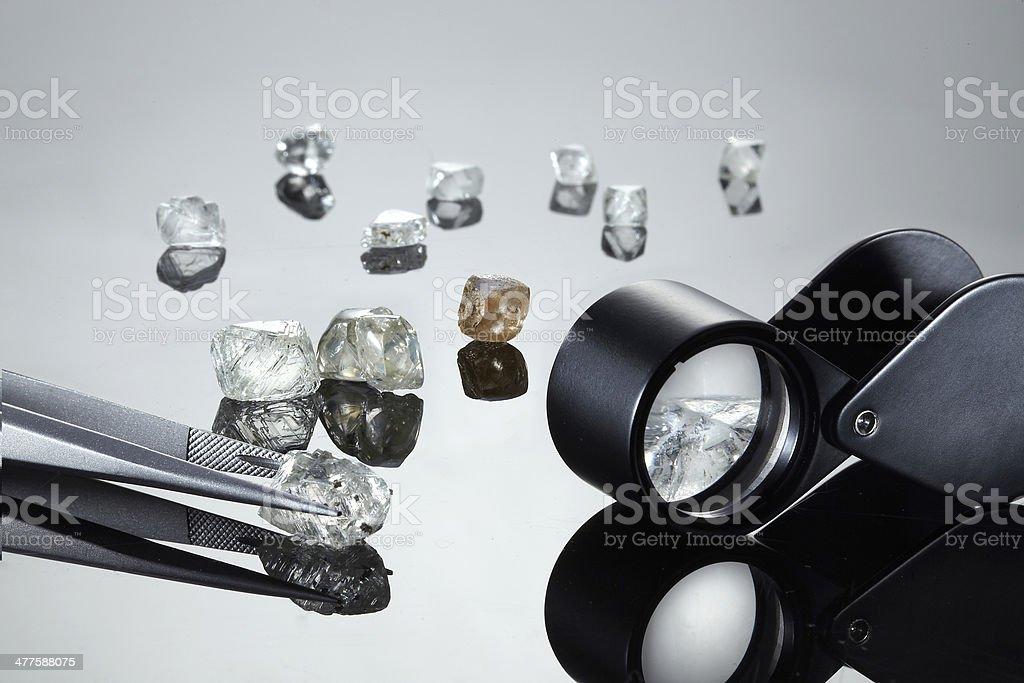 Uncut diamonds with tweezers and loupe stock photo