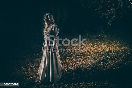 Woman dressed as witch standing in the night