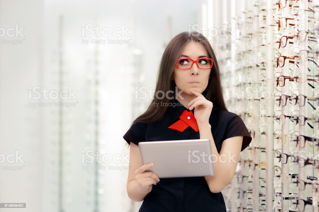 Undecided Woman with PC Tablet in Optical Store stock photo