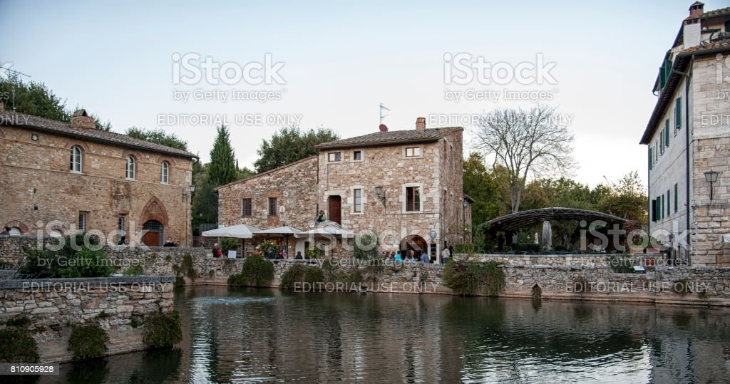 Undefined people in the old thermal baths in the medieval village Bagno Vignoni, Tuscany, Italy - Spa basin in the antique italian town. stock photo