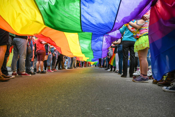 Under a LGBT Pride Flag Under a LGBT Pride Flag, taken at Exeter Pride Parade, public event. lgbtqi rights stock pictures, royalty-free photos & images