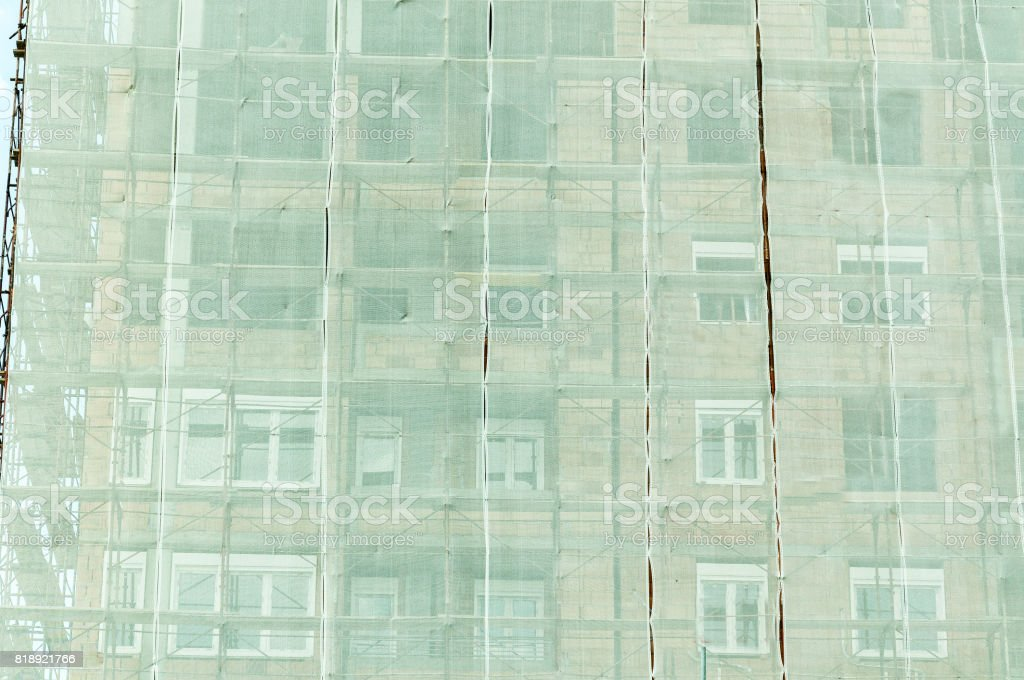 Under construction. Building construction site safety net and scaffolding on facade. Safety concept. stock photo