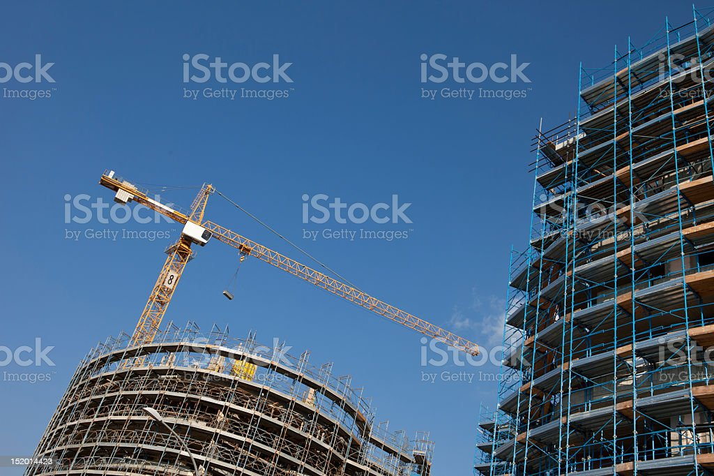 Under construction: buildings structure and cranes, blue sky stock photo