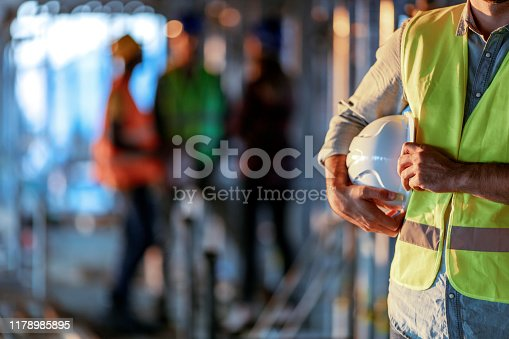 Man holding white helmet close up. Construction man worker with office and people in background. Close up of a construction worker's hand holding working helmet.