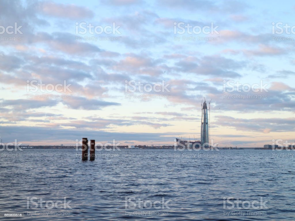 under construction skyscraper on the beach at sunset stock photo
