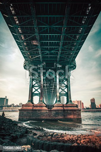 The view under Manhattan Bridge with river, near Brooklyn bridge park. The Manhattan Bridge is a suspension bridge that crosses the East River in New York City, connecting Lower Manhattan at Canal Street with Downtown Brooklyn at the Flatbush Avenue Extension.
