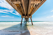 Under Okaloosa island fishing pier in Fort Walton Beach, Florida with wooden pillars green waves in Panhandle Gulf of Mexico during sunny day