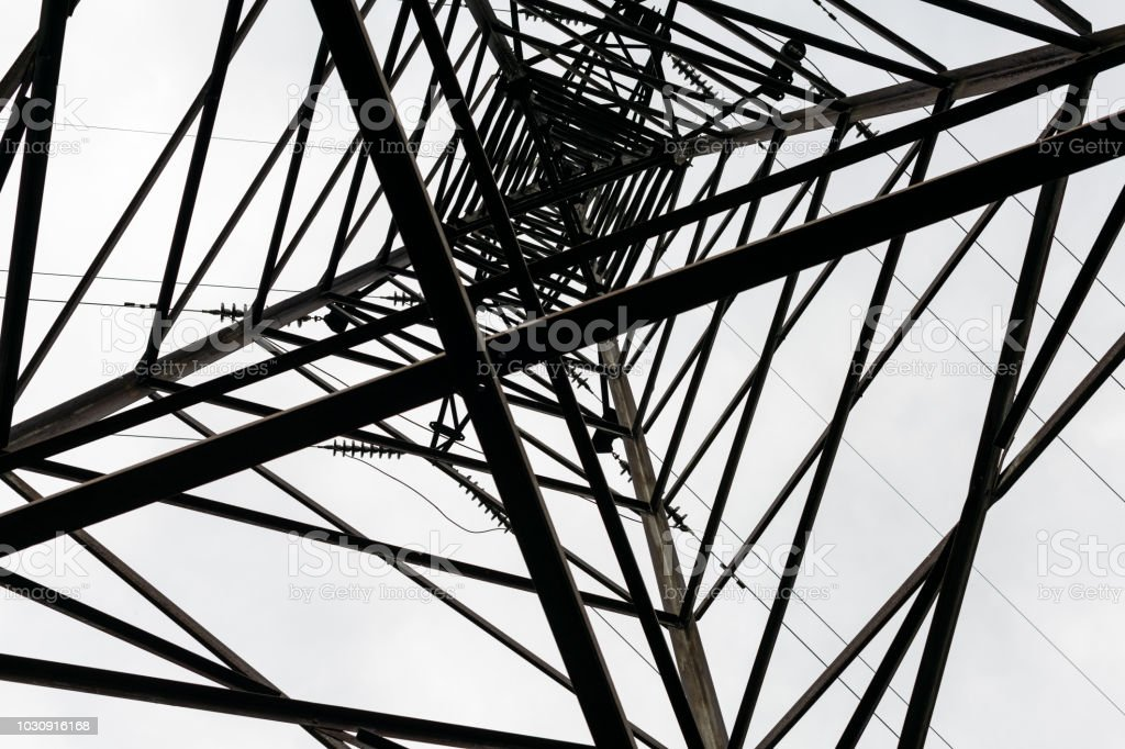 Under overhead high-voltage power line tower. View from bottom of...