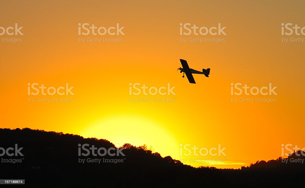 Under side of an airplane flying in an orange sky at sunset stock photo