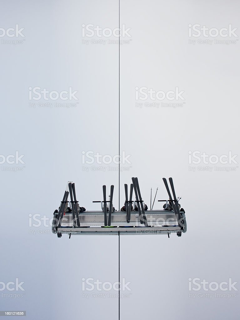 Under side view of skiers riding a ski lift stock photo
