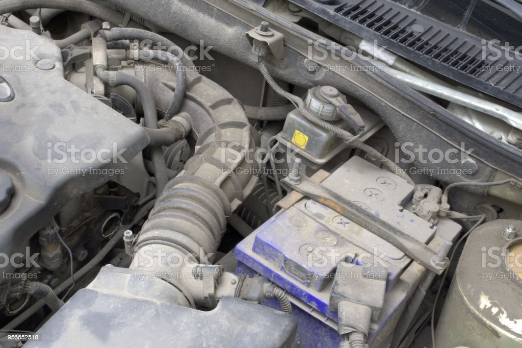under the hood. duct hose transfer of air intake system, lead-acid car battery in clamping lock, brake fluid reservoir and fragment of the engine. serviced components vehicle stock photo