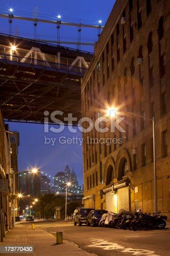 Empty streets of Dumbo Brooklyn under the Manhattan Bridge at night.