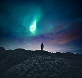 Woman standing on the coast and watching aurora borealis.
