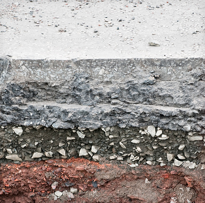 A cross section through a tarmac road surface, showing levels of rock and earth below.