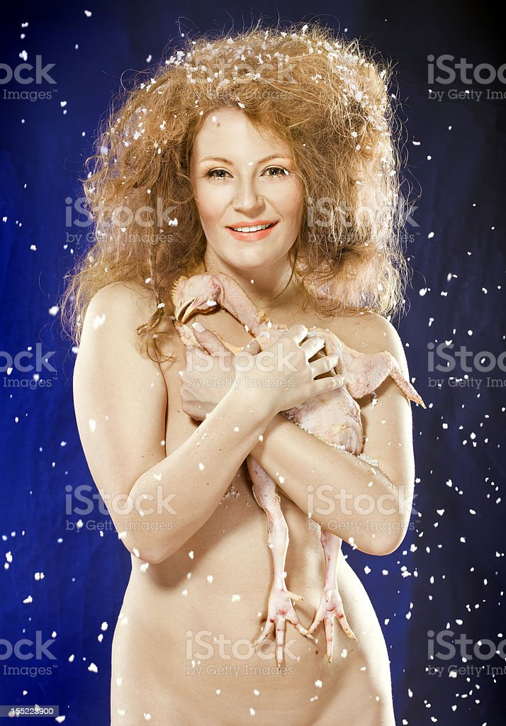 under the snow naked woman hugging embosom chicken stock photo