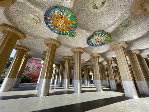 Under the stunning Park Guell in Barcelona with colorful mosaic and columns. Catalonia, Spain