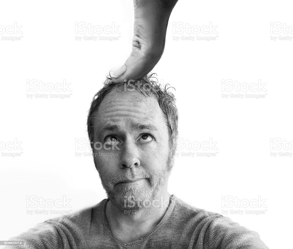 Under the thumb - oppressed man isolated on white. stock photo