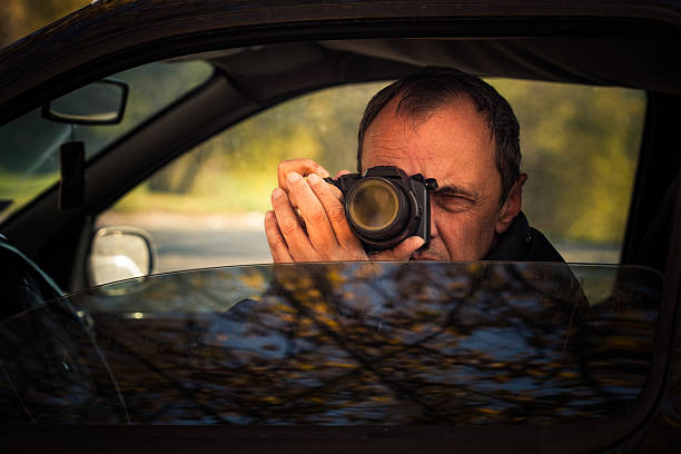 undercover man hidden in car take photo stock photo