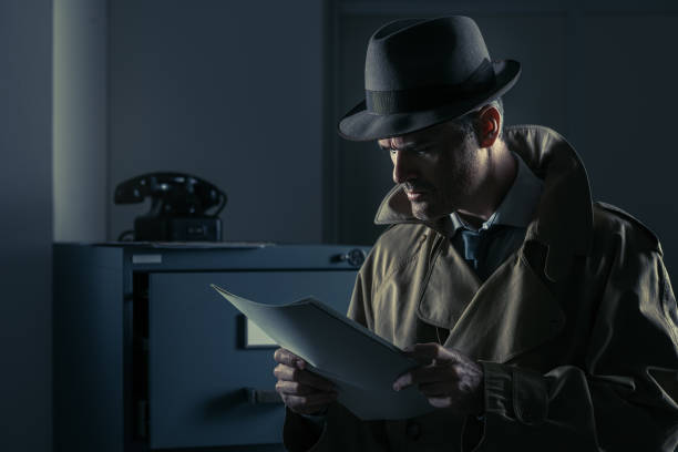 Undercover spy stealing files Vintage undercover agent stealing files in a corporate office late at night, security and data theft concept detective stock pictures, royalty-free photos & images