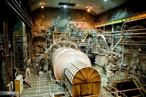 A twenty-foot diameter ball mill rotates at a copper mine's underground processing facility in Chile.  This process breaks copper-bearing ore from golf-ball sized pieces into dust. Dozens of other pumps, motors, ladders, cranes, lights, and scaffolding is visible surrounding this equipment.