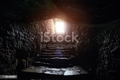 Underground passage under old medieval fortress. Old stone stairs to exit of tunnel.