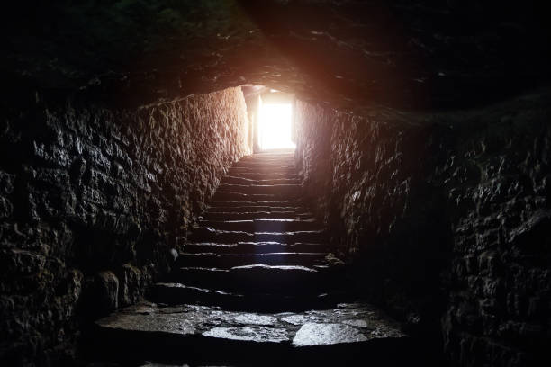 Underground passage under old medieval fortress. Old stone stairs to exit of tunnel stock photo