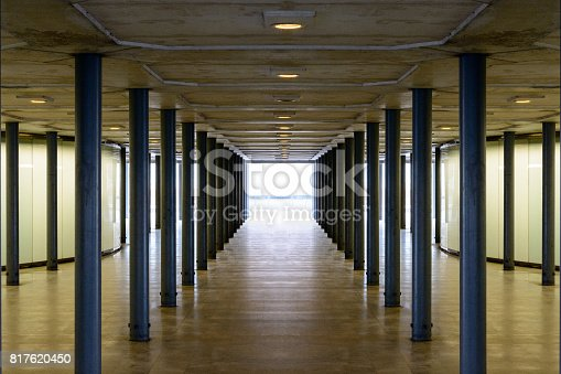 Underground pedestrian passage with alignments of metallic pillars, lighting walls, concrete ceiling and down lights.