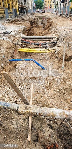 Underground excavating for pipes repair on urban street.