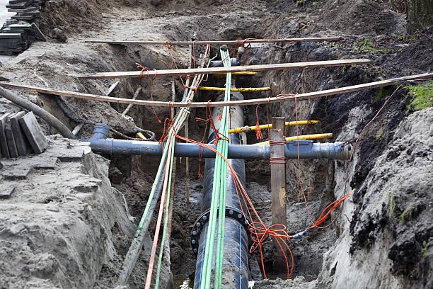 underground pipes and cables - unterirdisch stock-fotos und bilder