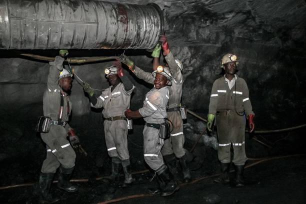 Underground Platinum miners fitting a ventilation pipe stock photo