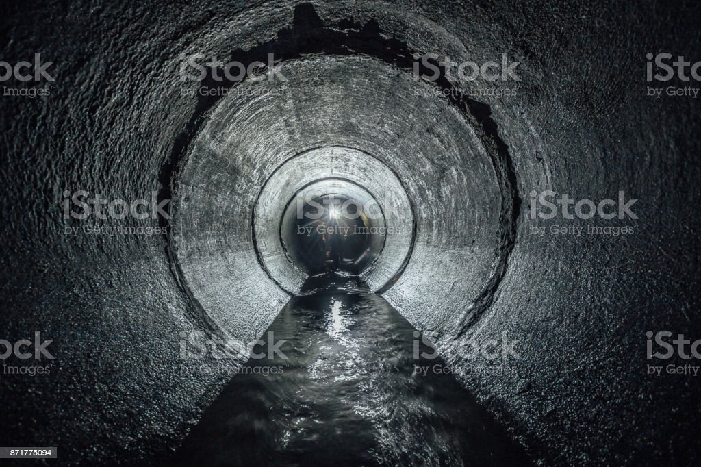 Underground river flowing in round concrete sewer tunnel. Sewage collector stock photo