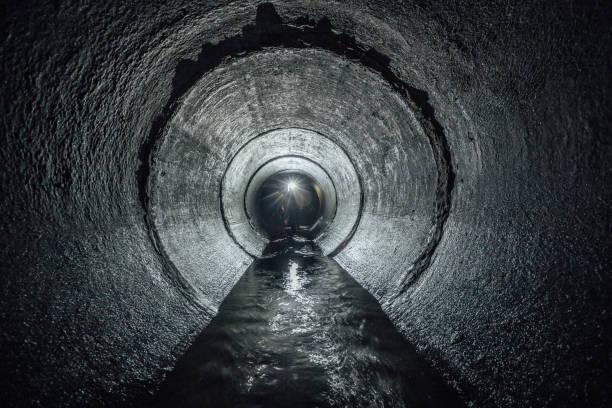 unterirdische fluss fließt in runde konkrete kanalisation tunnel. abwasser-sammler - tunnel stock-fotos und bilder