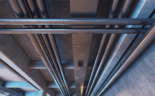 Pipes, tubes and air ducts hanging from a garage ceiling with concrete beams. Metal, aluminum and steel equipment. Engineering details. Modern industrial background with dim illumination. Digitally generated image.